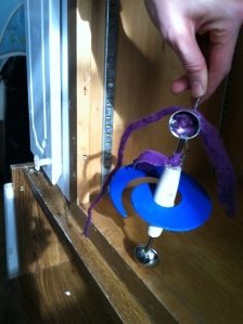 Painting the swirl blue helps and the purple yarn hair brings focus to the top circle. The little purple scarf adds color.