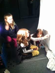 The girls who designed the puppets above, with a young admirer.