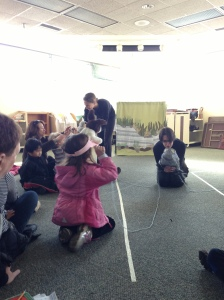 Anansi leaves spider webs of yarn with audience members playing the different animals