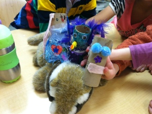 Three student made puppets hitch a ride on a chipmunk puppet that a teacher brought.