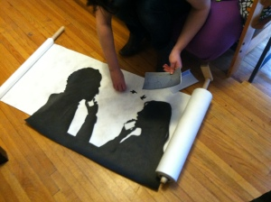 Amy is carefully placing the tiny paper birds between these two silhouettes.