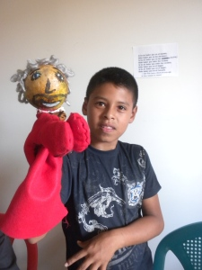 A teen from El Salvador with his hand puppet. The head is a gourd that grows locally.
