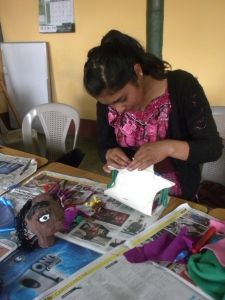 A student in Guatemala sews her puppet's body.
